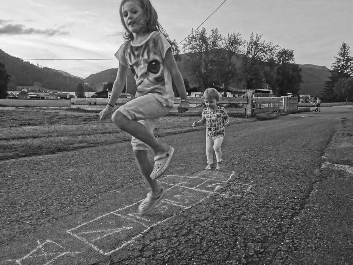 """Betina ucząca Telimenę, """"gry w klasy"""". W tle Feliks, który w St. Johann nauczył jeździć się na rowerze bez bocznych kółek, tu chyba zapatrzony na Stopniówkę"""